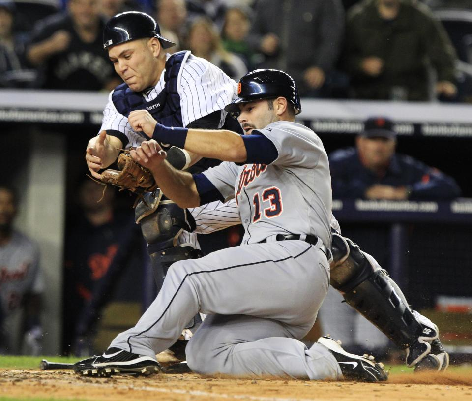 Detroit Tigers' Alex Avila (13) is tagged out at home plate by New York Yankees catcher Russell Martin in the fifth inning during the continuation of Game 1 of baseball's American League division series Saturday, Oct. 1, 2011, at Yankee Stadium in New York. (AP Photo/Frank Franklin II)