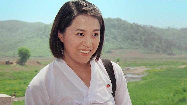 """In this image made out of film """"Comrade Kim Goes Flying"""" released by Another Dimension of An Idea/Koryo Group, Comrade Kim Yong Mi played by Han Jong Sim smiles in Korean dress.  It's a classic tale of a small town girl who follows her dreams to the big city. But in this case, the girl is a North Korean coal miner, the big city is Pyongyang and her dream is to become a high-flying trapeze artist. """"Comrade Kim Goes Flying,"""" a collaboration between a North Korean director and two European filmmakers, makes its world premiere Saturday, Sept. 8, 2012 at the Toronto International Film Festival before it heads to Pyongyang later this month for its North Korean debut. (AP Photo/Courtesy of Another Dimension of An Idea/Koryo Group) EDITORIAL USE ONLY"""