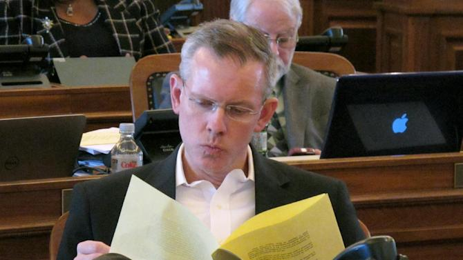 Kansas House Minority Leader Paul Davis, a Lawrence Democrat, reviews an explanation of a bill stripping cities and counties of their power to regulate guns, Saturday, April 5, 2014, at the Statehouse in Topeka, Kan. The House approved the legislation, 102-19, on Saturday, a day after the Senate passed it, 37-2. The measure goes next to Republican Gov. Sam Brownback. (AP Photo/John Hanna)