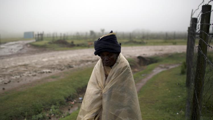 Woman uses plastic sheet to shelter from rain as she walks in village of Mvezo in South Africa's Eastern Cape Province, where Nelson Mandela was born