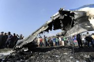 Onlookers and rescuers are seen near the wreckage of an Sita Air Dornier plane crash site in Manohara, on the outskirts of Kathmandu on September 28, 2012. The small passenger plane carrying 19 people crashed on the outskirts of the Nepalese capital, killing everyone on board