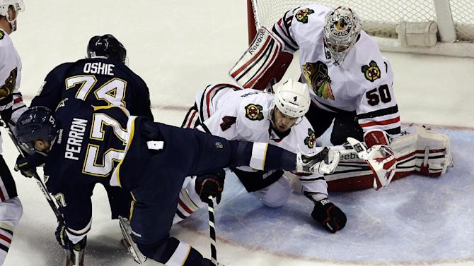 Chicago Blackhawks goalie Corey Crawford (50) and Niklas Hjalmarsson (4), of Sweden, try to smother a loose puck as St. Louis Blues' David Perron, front left, and T.J. Oshie get in on the play during the first period of an NHL hockey game, Thursday, Feb. 28, 2013, in St. Louis. (AP Photo/Jeff Roberson)