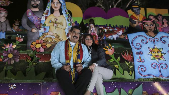 Venezuela's President Nicolas Maduro delivers his Christmas message beside his wife Cilia Flores at the Miraflores Palace in Caracas