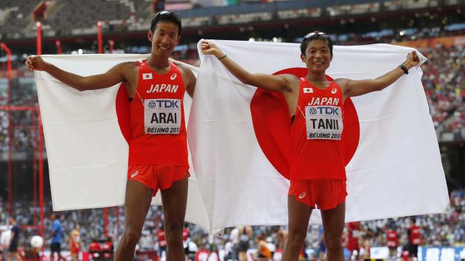 Arai and Tanii hold their national flag after the men's 50km race walk final at the 15th IAAF Championships in Beijing