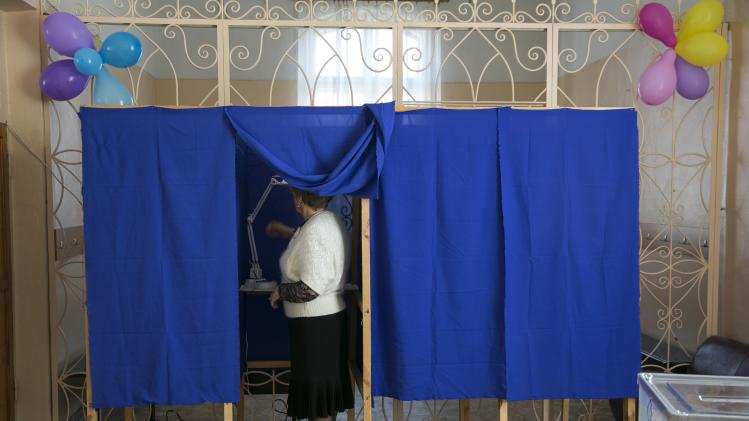 An election commission official checks a voting booth ahead of a referendum, inside a school in Sevastopol