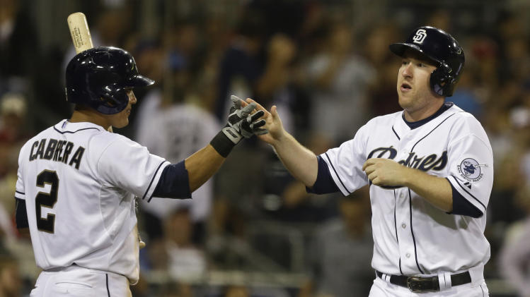 San Diego Padres' Jedd Gyorko is congratulated by Everth Cabrera after scoring the go ahead run against the St. Louis Cardinals in the sixth inning of a baseball game in San Diego, Monday, May 20, 2013. Gyorko scored from third when Padres batter Jesus Guzman was hit by a pitch with the bases loaded.  (AP Photo/Lenny Ignelzi)