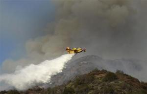 """An air tanker makes waters drops as firefighters battle a fast-moving California wildfire, so-called the """"Colby Fire"""", in the hills of Glendora"""