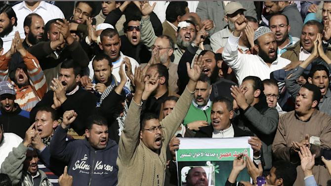 """Supporters of the Muslim Brotherhood and Egyptian President Mohammed Morsi, chant slogans during the funeral of three victims who were killed during Wednesday's clashes outside Al Azhar mosque, the highest Islamic Sunni institution, Friday, Dec. 7, 2012. During the funeral, thousands Islamist mourners chanted, """"with blood and soul, we redeem Islam,"""" pumping their fists in the air. """"Egypt is Islamic, it will not be secular, it will not be liberal,"""" they chanted as they walked in a funeral procession that filled streets around Al-Azhar mosque. (AP Photo/Hassan Ammar)"""