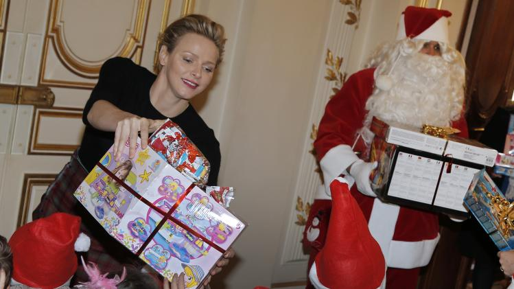 Princess Charlene of Monaco distributes gifts to children during the traditional Christmas tree ceremony at the Monaco Palace as part of Christmas holiday season in Monaco