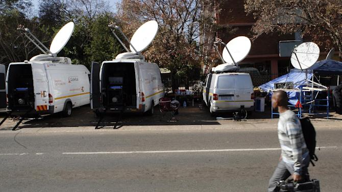 International and local news organizations stake outside the hospital in Pretoria, South Africa, Tuesday, June 11, 2013, where it is believed former president Nelson Mandela is being treated for a recurring lung infection, undergo searches at the entrance. Mandela was hospitalized Saturday with the government statement saying that Mandela remains in a serious but stable condition. (AP Photo/Themba Hadebe)