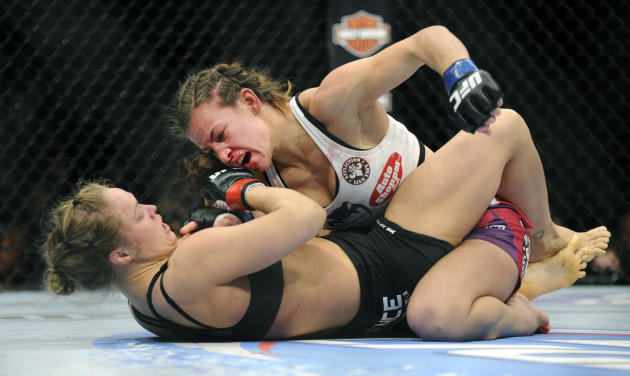 Miesha Tate, top, of Yakima, Wash., punches to Ronda Rousey of Venice, Calif., during the UFC 168 mixed martial arts middleweight championship bout during the UFC 168 mixed martial arts women's ba