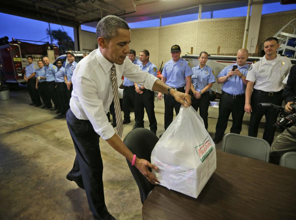 President Barack Obama delivers boxes of Krispy Kreme doughnuts, that he purchased nearby, to firefighters at Fire Station No. 14., during an unannounced visit, Thursday, Oct. 25, 2012, in Tampa, Fla. (AP Photo/Pablo Martinez Monsivais)