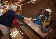 IMF chief Christine Lagarde (left) with two children in a school in Niger in 2011. Lagarde said in an interview with a British newspaper that she thinks more about poor Africans than struggling Greeks, who are the recipients of one of the IMF's largest-ever rescue loans, which comes with grueling reform conditions.