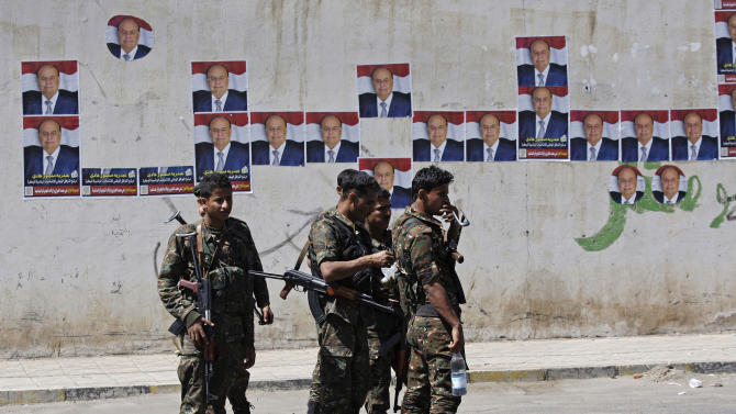 Yemeni soldiers stand during a pro-election rally in Sanaa, Yemen, Monday, Feb. 20, 2012. Campaign posters, background, show Yemen's Vice President Abed Rabbo Mansour Hadi. (AP Photo/Hani Mohammed)