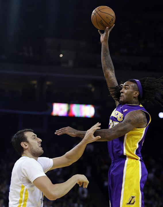 Los Angeles Lakers' Jordan Hill, right, shoots over Golden State Warriors' Andrew Bogut during the first half of an NBA basketball game Saturday, Dec. 21, 2013, in Oakland, Calif