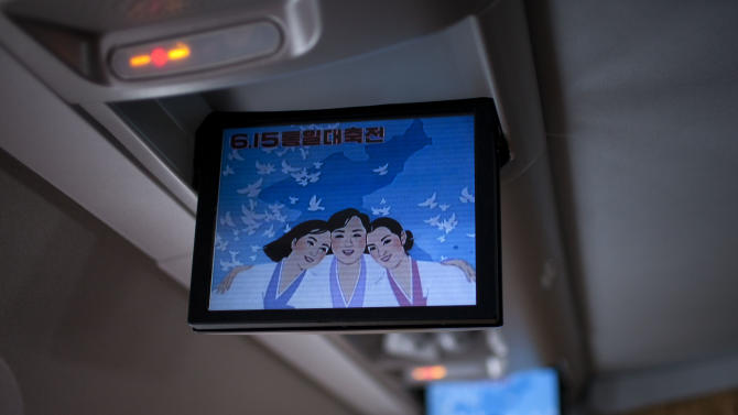 """In this Friday June 14, 2013 photo, a music video about a song called """"Reunification, June 15th"""" is shown on screens of an Air Koryo jet while on its way from Beijing to Pyongyang, North Korea. Korean on the screen read """"Celebration for the June 15 joint-declaration."""" Late North Korean leader Kim Jong Il and the late South Korean President Kim Dae Jung signed the June 15 declaration calling for the two Koreas to develop relations toward eventual reunification during a historic 2000 summit in Pyongyang. High-level talks between the Seoul and Pyongyang governments, the first in six years, were called off earlier in the week.(AP Photo/Alexander Yuan)"""