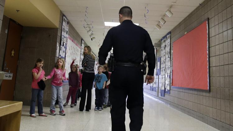 In a photo made Thursday, Feb. 21, 2013, police officer Jeff Strack walks the hallway as children watch him at Jordan Elementary School in Jordan, Minn. In what is believed to be the first of its kind nationwide, the small city south of Minneapolis is taking school security to a new level by setting up satellite offices inside the public school buildings. (AP Photo/Jim Mone)