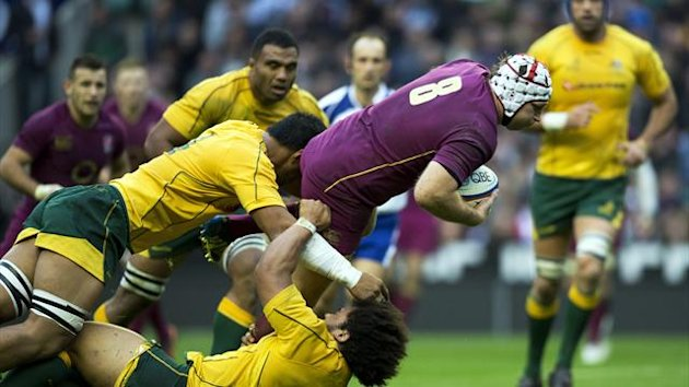 England's No. 8 Thomas Waldrom (R) tries to break a tackle from Australia's Hooker Tatafu Polota-Nau (bottom) during the International rugby union test match between England and Australia at Twickenham Stadium