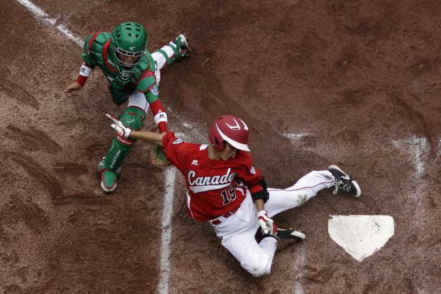 Vancouver, British Columbia's Thomas Neal, right, scores past Nuevo Laredo, Mexico's Marcelo Perez on a two-run double by Cortez D'Alessandro in the first inning of a pool play baseball game at the Li