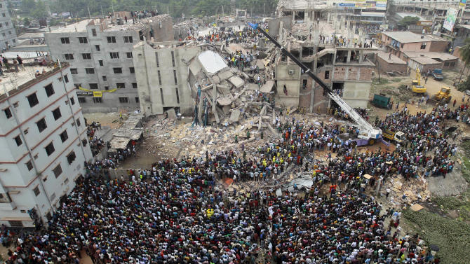 Bangladeshi people gather as rescuers look for survivors and victims at the site of a building that collapsed Wednesday in Savar, near Dhaka, Bangladesh,Thursday, April 25, 2013. By Thursday, the death toll reached at least 194 people as rescuers continued to search for injured and missing, after a huge section of an eight-story building that housed several garment factories splintered into a pile of concrete.  (AP Photo/A.M.Ahad)