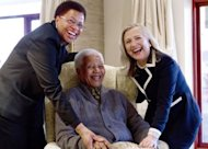 US Secretary of State Hillary Clinton poses for a photograph with Nelson Mandela, 94, former president of South Africa, and his wife Graca Machel at his home in Qunu, South Africa