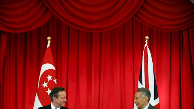Britain's Prime Minister David Cameron and his Singaporean counterpart Lee Hsien Loong speak after a signing of memorandum on Cyber Security Cooperation at the Istana in Singapore