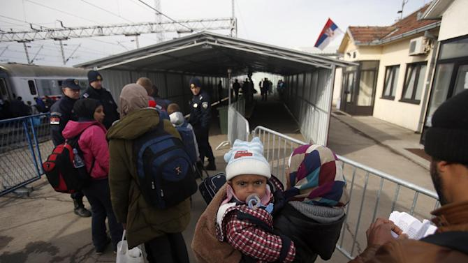 Migrants wait to board a train at the train station in Sid, about 100 km (62 miles) west from Belgrade, Serbia, during U.S. Sen. John McCain, unseen, visit on Friday, Feb. 12, 2016.  Sen. McCain and a U.S. Congress delegation pledged assistance to Serbia and other countries along the Balkan migrant route. (AP Photo/Darko Vojinovic)