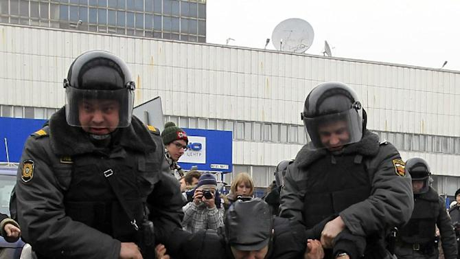 """In this Sunday, March 18, 2012 photo, police officers detain a protester outside the Kremlin-loyal NTV television station in Moscow.  Russian opposition and human rights groups on Monday, Nov. 19, 2012,  urged Western consumer products giants to stop """"financing politically motivated persecution"""" by advertising on a Kremlin-friendly TV network known for its biased coverage of government critics and demonstrations against President Vladimir Putin. In the wake of unprecedented anti-Putin protests that followed last December's rigged parliament vote and Putin's return to the Kremlin in May, NTV has run dozens of news reports, talk shows and pseudo-documentaries accusing opposition leaders of plotting coups and terrorist attacks, of receiving money from Western governments, and of hiring migrant workers and neo-Nazis to participate in anti-Putin rallies.  (AP Photo/Sergey Ponomarev)"""