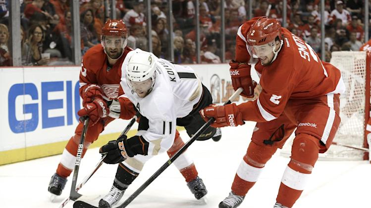 Anaheim Ducks center Saku Koivu (11), of Finland, is defended by Detroit Red Wings defenseman Kyle Quincey (27) and defenseman Brendan Smith (2) in the first period in Game 6 of a first-round NHL hockey Stanley Cup playoff series in Detroit, Friday, May 10, 2013. (AP Photo/Paul Sancya)