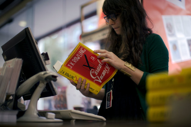 An employee looks at a copy of the &quot;The Casual Vacancy&quot; by author J.K. Rowling at a book store in London, Thursday, Sept. 27, 2012.  British bookshops are opening their doors early as Harry Potter aut