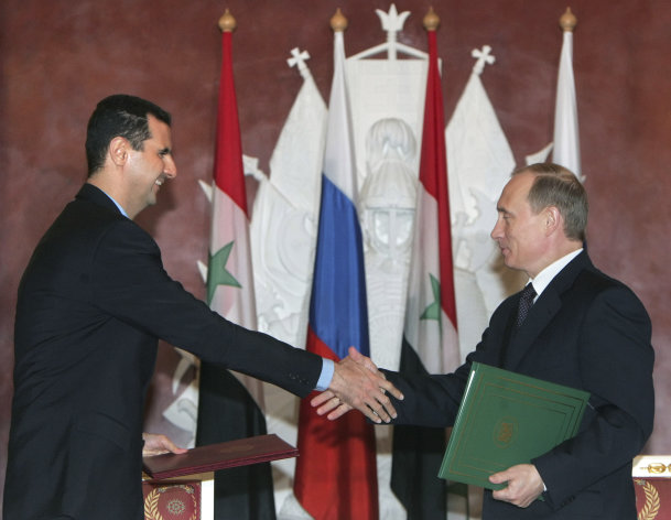 FILE - In this Jan. 25, 2005 file photo, Syrian President Bashar Assad, left, and Russian President Vladimir Putin shake hands during a signing ceremony in the Kremlin, Moscow. Russia has shielded Syrian President Bashar Assads regime, its last ally in the Arab world, from international sanctions and has continued to provide it with weapons despite international outrage. It has shipped billions of dollars worth of missiles, combat jets, tanks, artillery and other military gear to Syria over more than four decades. (AP Photo/Sergei Chirikov, Pool-File)