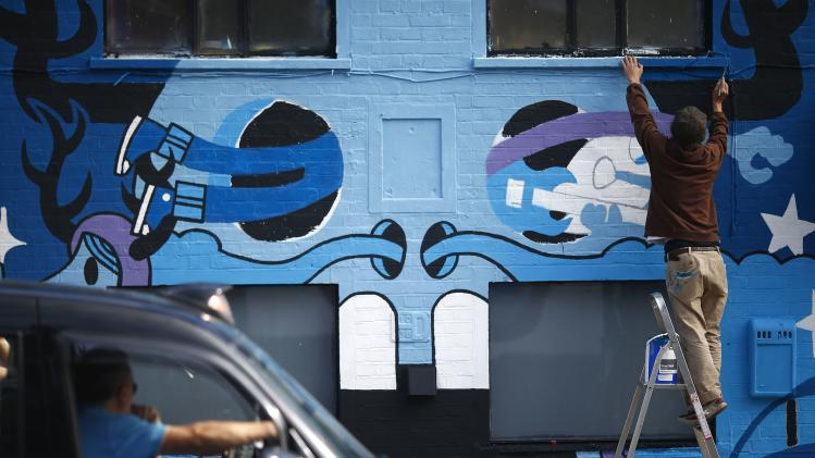 A taxi driver watches artist Pete Fowler putting the finishing touches to his mural on a building in east London