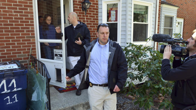 FBI agents leave the home of, from left behind the door, Carlos and Melida Arredondo in the Roslindale neighborhood of Boston, Wednesday, April 17, 2013. Arredondo, a peace activist who's son was killed during the Iraq war, was near the explosions and assisted victims after a  pair of bombs exploded at the finish line of the Boston Marathon Monday. (AP Photo/Josh Reynolds)
