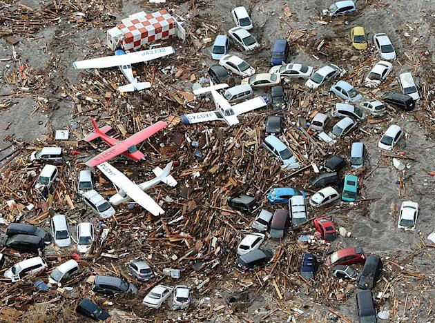Light planes and vehicles sit among debris at Sendai airport, northern Japan.
