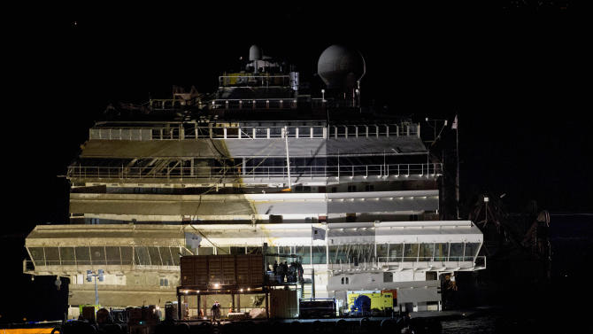 "The Costa Concordia rests upright on the Tuscan Island of Giglio, Italy, early Tuesday morning, Sept. 17, 2013. The crippled cruise ship was pulled completely upright early Tuesday after a complicated, 19-hour operation to wrench it from its side where it capsized last year off Tuscany, with officials declaring it a ""perfect"" end to a daring and unprecedented engineering feat. (AP Photo/Andrew Medichini)"