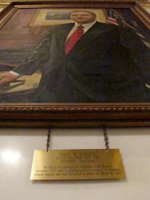 The plaque hanging in the Pennsylvania Capitol below the official portrait of former House Speaker John Perzel and three other former top state lawmakers in Harrisburg, Pa. now includes information about their criminal histories. Plaques that add those details to the dates the four men served were hung Tuesday, July 15, 2014. (AP Photo/Marc Levy)