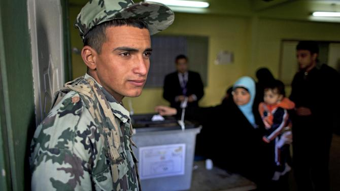 An Egyptian army soldier guards the site of a polling station as a women casts her vote during the second round of a referendum on a disputed constitution drafted by Islamist supporters of president Mohammed Morsi, in Giza, Egypt, Saturday, Dec. 22, 2012.  Egyptians voted on Saturday in the final phase of a referendum on a proposed new constitution that has polarized the nation, with little indication that the result of the vote will end the political crisis in which the country is mired. (AP Photo/Nasser Nasser)
