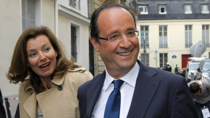 FILE This  Thursday, April 5, 2012 file photo shows French Socialist Party candidate for the upcoming French presidential election Francois Hollande and his companion French journalist Valerie Trierweiler, left, leaving the Paris Institute of Political Studies, or Sciences Po in Paris. The last time France voted for president, Francois Hollande was a portly, smiley man with a wishy-washy image playing second fiddle to Segolene Royal, his Socialist party's candidate and the mother of his four kids. Now he's a man with a trim waistline and promising future who managed a tough presidential debate with the air of, well, a president. (AP Photo/Jacques Brinon, file)