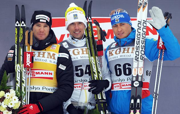 Winner Sweden's Johann Olsson (C), second-placed Switzerland's Dario Cologna (L) and third-placed Russia's Alexander Legkov pose on the podium of the men's 15 km classic race during the 15th Cross-cou