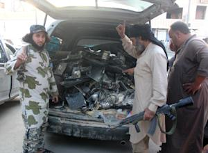 Fighters from the Islamic State group load a van with…