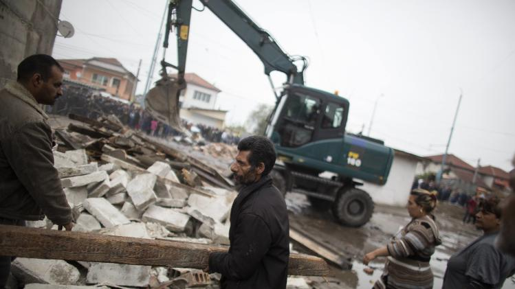 Bulgarian Roma men salvage materials as an excavator demolishes a shack in a Roma suburb in the city of Plovdiv
