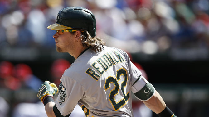 Oakland Athletics' Josh Reddick follows through for a single against the Texas Rangers during the seventh inning of a baseball game, Sunday, May 3, 2015, in Arlington, Texas. (AP Photo/Jim Cowsert)