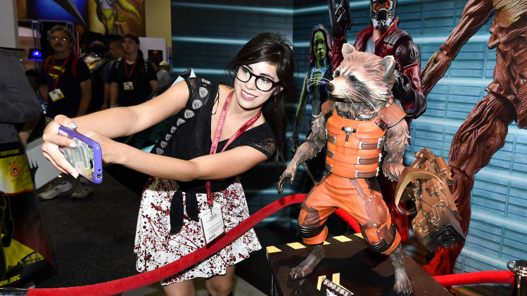Monique Soto takes a selife with a Guardians of the Galaxy Rocket Racoon figurine during preview night at the 2014 Comic-Con International Convention held Wednesday, July 23, 2014 in San Diego. (Photo by Denis Poroy/Invision/AP)