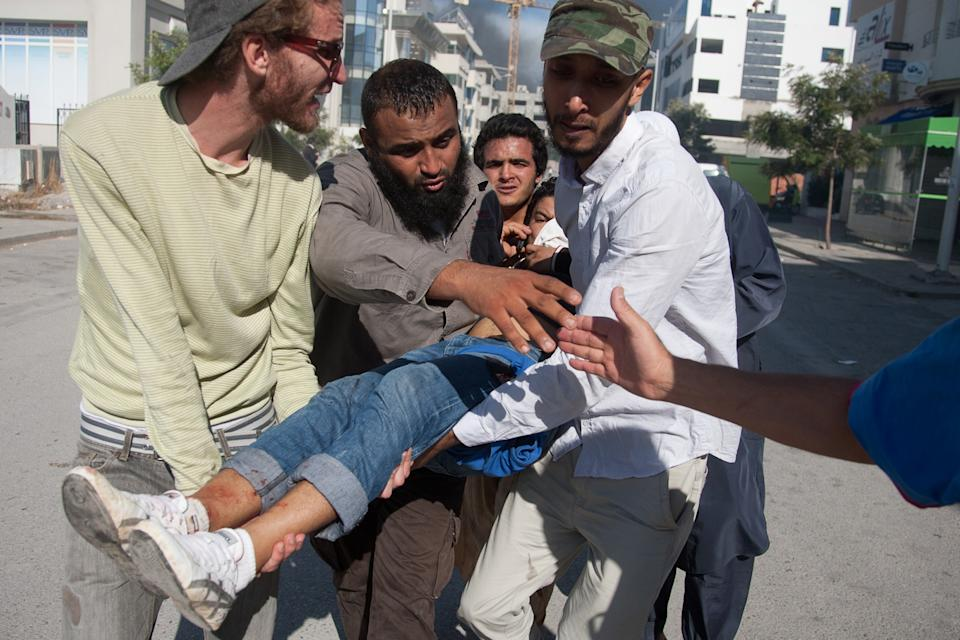 Tunisian protesters carry away a wounded man during clashes outside the U.S. embassy in Tunis, Friday, Sept. 14, 2012. Thousands of demonstrators massed outside the embassy and several were seen climbing the outer wall of the embassy grounds, an Associated Press reporter on the scene said. (AP Photo/Amine Landoulsi)