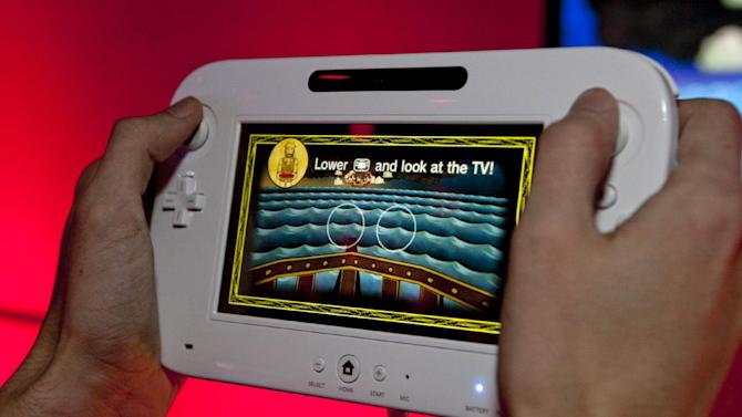 "FILE - In this June 8, 2011 photo, Nintendo's video game console:Wii U is demonstrated at the Nintendo booth at the 2011 Electronic Entertainment Expo in Los Angeles. At this year's Electronic Entertainment Expo, Nintendo is expected to show off exactly what kinds of games will be available for its new touchpad-powered Wii U console, while other gamemakers will hype the latest installments in their ""Call of Duty,"" ""Halo"" and ""God of War"" franchises.  (AP Photo/Damian Dovarganes, file)"