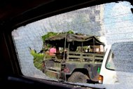 A Lebanese army jeep is seen through the shattered windscreen of a car following overnight clashes in Beirut as violence spills over from Syria
