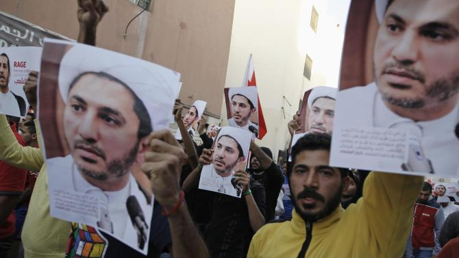 Protesters shout anti-government slogans holding placards with an image of Salman as they demonstrate for him in the village of Bilad Al Qadeem