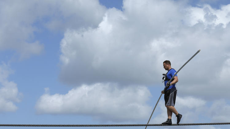 High wire performer Nik Wallenda concentrates as he walks across a wire during practice Tuesday, June 18, 2013 in Sarasota, Fla. Wallenda, a seventh generation high-wire walker, will attempt to walk across the Grand Canyon on Sunday, June 23, 2013. (AP Photo/Chris O'Meara)