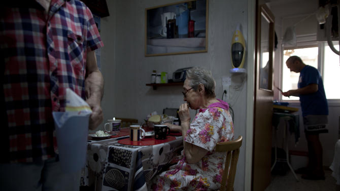 In this Oct. 31, 2012 photo, Bella Perlin, center, and Avraham Shapiro, left, Belarusian immigrants, eat breakfast in their home in Hadera, northern Israel. They emigrated to Israel in 1991 at the height of the wave of immigration from the former Soviet Union. (AP Photo/Oded Balilty)