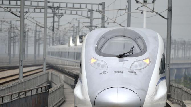 In this photo released by China's Xinhua news agency, a bullet train G80 leaves for Beijing from the Guangzhou South Railway Station in Guangzhou, capital of south China's Guangdong Province, Wednesday, Dec. 26, 2012. China has opened the world's longest high-speed rail line, which runs 2,298 kilometers (1,428 miles) from the country's capital in the north to Guangzhou, an economic hub in the Pearl River delta in southern China. (AP Photo/Xinhua, Chen Yehua) NO SALES